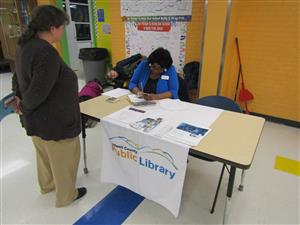 Representative from the county library, signing up students for their new library cards.