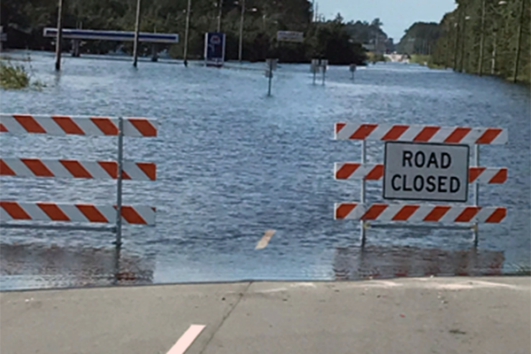 A flooded road with road closed sign