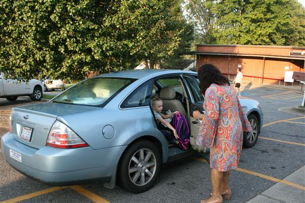 Principal Carol Sturgis opens the car door for one of her students returning to school.